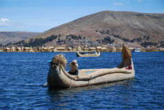 The boat on Lake Titicaca in Peru. Islanders rowing a boat on Lake Titicaca in Peru Royalty Free Stock Photography