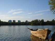 Boat at lakeside. Old boat at lakeside in Titan park in Bucharest, with blocks of apartments in the background Royalty Free Stock Photos