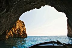 Boat in a large sea cave Stock Image