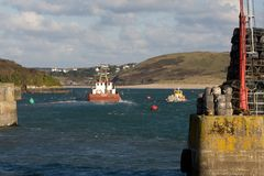 Padstow harbour fishing boats. A boat leaves Padstow Harbour heading out to sea along the River Camel Estuary with the harbour wall and lobster pots in the Stock Photo