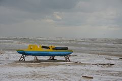 Boat left on the snowy beach in winter with the rough sea stock image