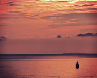 Boat lies at anchor at sunset with red sky and red sea waters Stock Photos