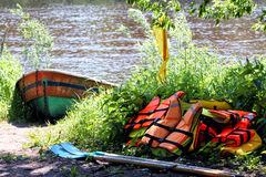 Boat and life jackets. On the river bank Stock Photos