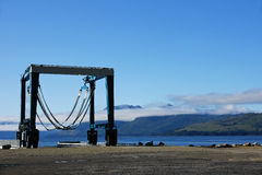 Boat Lift. A boat lift sits by a pier on a rare sunny day in Hoonah, Alaska amidst the rugged mountain scenery of the region Stock Photos