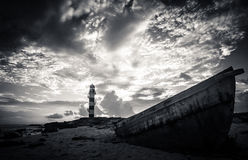 Boat by a lighthouse Stock Images