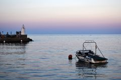 Boat and lighthouse. Small motor boat near the coast at sunset stock photo