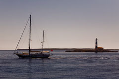 Boat And Lighthouse At Sunset. A boat slowly passing a lighthouse somewhere in the sea street between the isle of Ibiza and the isle of Formentera, both part of stock photo