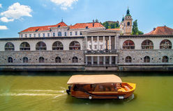 Boat on Ljubljanica river and St. Nicholas church in the backgro Royalty Free Stock Images