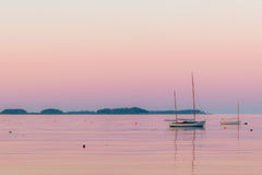 A boat and lobster buoys in the calm sea at dusk Stock Photography