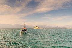 Boat with local people and tourists going to Bourtzi castle for a tour at Nafplio in Greece. Stock Photo