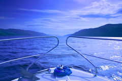 Boat on Loch Ness. Scenic view from rear of boat on Loch Ness with blue sky and cloudscape background stock photos