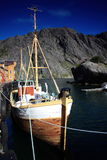 Boat in the lofoten. Cliff, sea and boat moored in a port of the lofoten islands Stock Images