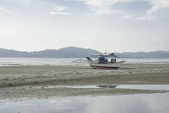 Boat lying on an empty beach. In Port Barton, Philippines, South East Asia Stock Image