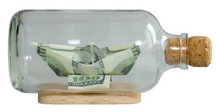 The boat made ​​of dollars. In a bottle capped Royalty Free Stock Photo
