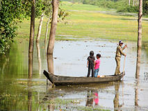Boat with a man and children in the river in jungle, Cambodia Stock Photos