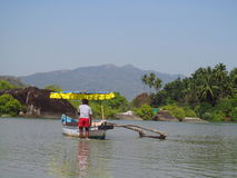Boat with a man in the river in jungle in India Stock Image