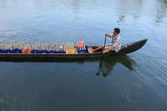 A boat man transport soft drink bottles in his boat Royalty Free Stock Image