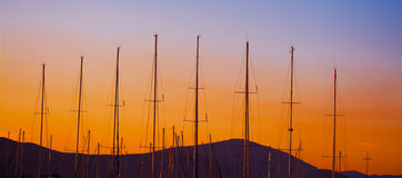 Boat masts silhouette under a colorful sunset Stock Image
