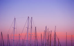 Boat masts under a pink and orange sunset Stock Photography