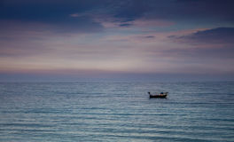 A boat in a Mediterranean beach of Ionian Sea at sunset - Bova Marina, Calabria, Italy Royalty Free Stock Photos