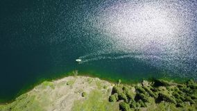 A boat in the middle of a mountain lake. Landscape mountain lake in the forest. stock video footage
