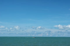 Boat in middle of ocean with cloudy sky Royalty Free Stock Photos