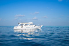 Boat in the middle of ocean. White boat parking still in the middle of blue ocean Royalty Free Stock Photos