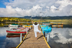 On boat moorage woman performs yoga Stock Image