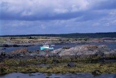 Boat Moored in Arichat Harbor, Nova Scotia. Aqua and white lobster boat anchored in Arichat harbor, Nova Scotia. It's low tide with rocks and seaweed covering Royalty Free Stock Image