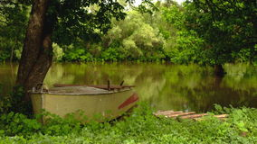 Boat moored on the banks of the river stock video footage