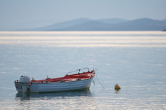 Boat moored on calm sea. Scenic view of wooden boat with outboard motor moored on calm sea, Halkidiki coastline in background, Greece Stock Photography