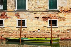 Venetian Curbside Parking. A boat moored in a canal along a brick building in Venice Royalty Free Stock Images