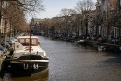 Boat moored in a canal in Amsterdam Netherlands. March 2015. Landscape format stock photo