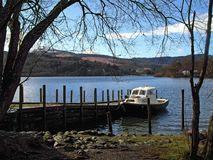 Boat moored on Derwent Water. Scenic view of Derwent Water with boat moored by pier in foreground, Lake District National Park, Cumbria, England Stock Image
