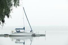 Boat moored at jetty in heavy fog Stock Photos