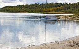 Boat moored on lake. Single boat moored on lake with forest in background Stock Photography