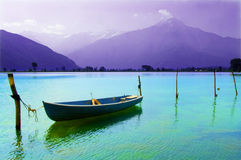 Boat moored in the lake. Boat berthed in the lake surrounded by mountains Royalty Free Stock Photo