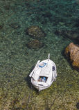 Boat moored in a rocky cove Royalty Free Stock Photo