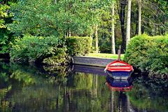 Boat moored to banks in park Royalty Free Stock Photo