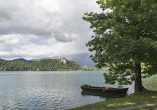 Boat moored in tree shade on Lake Bled. Stock Image