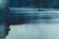 Boat in the morning fog. Lonely boat on a slow river in the morning mist Royalty Free Stock Photo