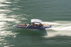 Boat in motion on green water. Boat in motion with wake on green water and people on board Stock Photo
