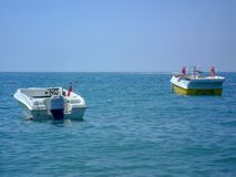 A boat with a motor moored with a view of the horizon royalty free stock photo
