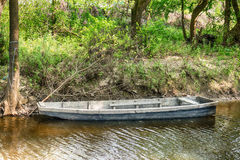 Boat in mountain stream in green forest at spring time Royalty Free Stock Image