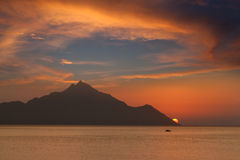 Boat and mountain towards the sun at dawn