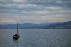 Boat with mountains. A small boat sailing across a lake in Switzerland with a backdrop of snowy mountains stock images