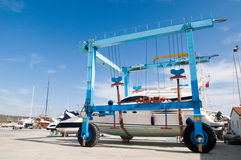 Boat on movable crane. A view of a luxury boat being transported on land at a marina by large moving crane Stock Photo