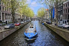 Boat on canal in Amsterdam. A boat moving along a canal in Amsterdam, Netherlands royalty free stock photo