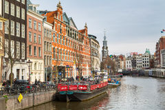 Boat, Munttoren Clock Tower and flower market in Amsterdam canal in Holland Royalty Free Stock Photo