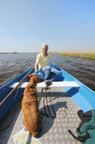 With boat in nature. Senior man is with boat and dog in nature stock photo